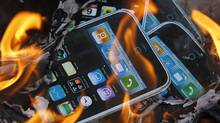 Cardboard cutouts resembling iPhones are sent on fire by labor activists near the Foxconn office in Hong Kong Tuesday, May 25, 2010. (Kin Cheung/AP/Kin Cheung)