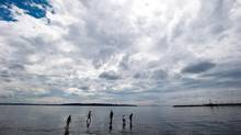 A man and children are silhouetted while standing in the waters of Semiahmoo Bay as rain clouds move into the area in White Rock, B.C., on August 26, 2013. A new report reveals that the overall physical activity levels of Canadian kids are lagging behind those of youngsters from other nations. (DARRYL DYCK/THE CANADIAN PRESS)
