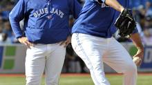 Toronto Blue Jays manager John Farrell (L) watches pitcher Ricky Romero throw during the third inning of their MLB American League baseball game against the New York Yankees in Toronto September 29, 2012. (MIKE CASSESE/REUTERS)
