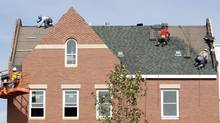 Builders work at the roof of a new housing construction site in Alexandria, Virginia October 17, 2012. (KEVIN LAMARQUE/REUTERS)