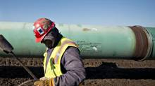 A worker carries a torch after heating a pipe joint during construction of the Gulf Coast Project pipeline in Atoka, Okla., on March 11, 2013. The Gulf Coast Project is part of the Keystone XL pipeline project. (Daniel Acker/Bloomberg)