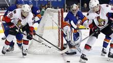 Ottawa Senators left wing Ryan Dzingel and Senators centre Tommy Wingels look to control the puck in front of New York Islanders goalie Thomas Greisson April 9, 2017. (Adam Hunger/The Associated Press)