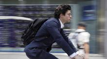 A man cycles past in front of an electronic stock board of a securities firm in Tokyo in this file photo. (Koji Sasahara/AP)