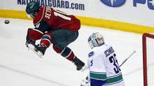 Minnesota Wild right wing Devin Setoguchi tries to screen Vancouver Canucks goalie Cory Schneider during the second period of their NHL hockey game in St. Paul, Minnesota March 19, 2012. (Reuters)