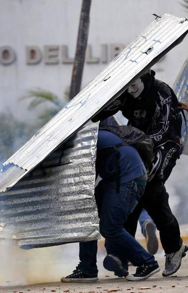 Anti-government protesters shield themselves during a rally in Caracas March 2, 2014. While many Venezuelans went to the beach to enjoy the Carnival holiday, thousands of anti-government demonstrators marched in the capital on Sunday, trying to keep up the momentum from weeks of protests demanding President Nicolas Maduro resign. (JORGE SILVA/REUTERS)