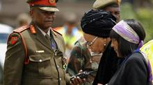 Nelson Mandela's widow Graca Machel, second left, holds her granddaughter Ndileka's hand as family members arrive ahead of the former South African president's casket at the Mthata airport in the Eastern Cape province of South Africa on Dec. 14, 2013. (Siphiwe Sibeko/AP)