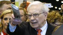 Berkshire Hathaway CEO Warren Buffett prepares to throw a newspaper in a competition just before the company's annual meeting in Omaha on May 4, 2013. (RICK WILKING/REUTERS)