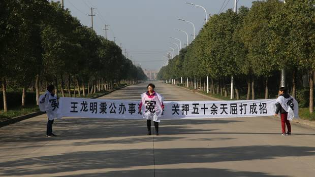 Jean Zou holds a protest banner on a street in Wuhu, China, near where her husband was detained. It reads, in part: 'Confession under torture after more than 50 days in detention.'