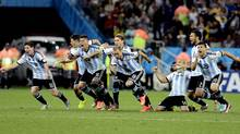 Argentine players react after Maxi Rodriguez scored the winning goal during a penalty shootout after extra time during the World Cup semi-final soccer match between the Netherlands and Argentina at the Itaquerao Stadium in Sao Paulo Brazil, Wednesday, July 9, 2014. (Associated Press)