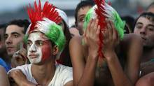 Italian supporters react after their team lost the Euro 2012 final soccer match against Spain at the ancient Circo Massimo in Rome July 1, 2012. (GIAMPIERO SPOSITO/REUTERS)