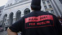 "A Muslim man stands outside the court in Putrajaya outside Kuala Lumpur June 23, 2014. Malaysia's Federal Court on Monday rejected an application for leave by the Catholic Church to challenge a Court of Appeal decision to prohibit the weekly Herald Bahasa Malaysia section from using the word ""Allah"". (SAMSUL SAID/REUTERS)"