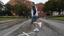 A visitor to Dealey Plaza runs across Elm Street where the X marks the spot where the fatal shot hit President John F. Kennedy as his motorcade drove through Dealey Plaza in Dallas. (Mark Graham)