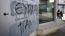 Graffiti is seen on the wall of a Laiki Bank, branch in Nicosia, Cyprus. (Simon Dawson/Bloomberg)