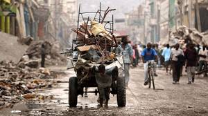 A Haitian man pulls a load of salvaged metal through the rubble in Port-au-Prince on February 3, 2010 .