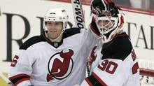 New Jersey Devils defenceman Andy Greene congratulates goalie Martin Brodeur on his 104th career shutout, the most in NHL history, after they defeated the Pittsburgh Penguins in Pittsburgh on Monday. (JASON COHN)