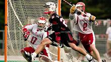 Casey Powell (centre) of the United States eludes Canada's Tom Phair to get a shot on Canadian goaltender Chris Sanderson (GEOFF ROBINS/CP)
