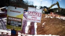 """A sign warning of a high pressure petroleum pipeline is seen on the """"Line 9"""" Enbridge oil pipeline as it is worked on in East Don Parkland in Toronto on March 6, 2014. (MARK BLINCH/REUTERS)"""