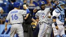 Toronto Blue Jays' Jose Reyes, center, acknowledges teammate Steve Tolleson after his single scored Reyes and Dan Johnson in front of Tampa Bay Rays catcher Jose Molina during the ninth inning of a baseball game Friday, July 11, 2014, in St. Petersburg, Fla. (MIKE CARLSON/AP)