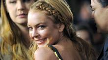 """This April 11, 2013 file photo shows actress Lindsay Lohan, a cast member in """"Scary Movie V,"""" at the premiere of the film in Los Angeles. Lohan is suing the makers of the """"Grand Theft Auto"""" video games. The actress says the latest installment used her image and created a character based on her without her permission. Lohan's lawsuit was filed Wednesday in a Manhattan court. """"Grand Theft Auto V"""" game maker Take-Two Interactive Software Inc. and subsidiary Rockstar Games declined to comment. (CHRIS PIZZELLO/INVISION/ASSOCIATED PRESS)"""