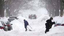 People clear snow from around their cars on a street in Montreal Sunday, December 22, 2013, as a winter storm warning has been issued for the region. (Graham Hughes/THE CANADIAN PRESS)