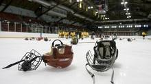 Helmets, gloves, and sticks litter the ice after being discarded by the winning team during their end-of-game celebrations. (Peter Power/The Globe and Mail)