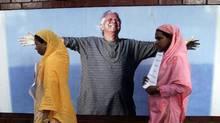 Grameen Bank employees walk past a portrait of Nobel laurate Muhammad Yunus in Dhaka. (Andrew Biraj/REUTERS)