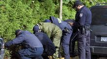 RCMP officers search the property surrounding an apartment building where six people died in a mulitple homicide in Surrey, B.C. Wednesday, Oct. 24, 2007. (Jonathan Hayward/THE CANADIAN PRESS)