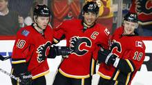 Calgary Flames' Jarome Iginla, centre, celebrates his goal with teammates Alex Tanguay, left, and Matt Stajan during second period NHL hockey action against the Phoenix Coyotes in Calgary, Alta., Thursday, March 15, 2012. (Jeff McIntosh/THE CANADIAN PRESS)
