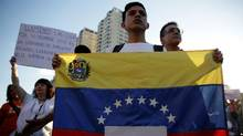 "An opposition supporter holds a Venezuelan flag with a sign that reads ""No more dictatorship"" during a protest against Venezuelan President Nicolas Maduro's government, in Caracas, Venezuela, on March 30, 2017. (MARCO BELLO/REUTERS)"