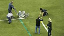 An official paints the lines around the eighteen yard box prior to the MLS Eastern Conference final between the Montreal Impact and Toronto FC at the Olympic Stadium in Montreal, Tuesday, November 22, 2016. Kickoff of the highly-anticipated all-Canadian playoff match was delayed 40 minutes as both boxes had to be widened to meet regulation size. (Graham Hughes/THE CANADIAN PRESS)