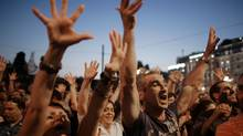 Greek protesters raise their hands in the traditional Greek insult gesture at Syntagma square in front of the Greek Parliament on June 21, 2011 in central Athens, Greece. (Milos Bicanski/Getty Images)