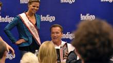 """Arnold Schwarzenegger signing copies of his new autobiography """"Total Recall"""" for Miss Canada 2012 Jaclyn Miles at Indigo in Toronto October 4, 2012. (Mike Cassese)"""