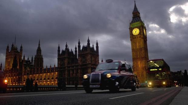 A bus and taxi pass Big Ben on Westminster Bridge in London, March 10, 2012. (KIERAN DOHERTY/Reuters)