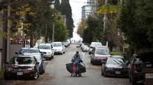 A homeless man walks through a back lane in the West End neighbourhood in Vancouver, British Columbia, Saturday, November 16, 2013. (Rafal Gerszak For The Globe and Mail)