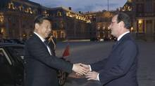Chinese President Xi Jinping, left, is welcomed by French President François Hollande, right, at the Chateau de Versailles, in Versailles, west of Paris, for a concert and dinner March 27, 2014. (Michel Euler/Associated Press)