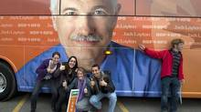 Supporters pose for photos by NDP Leader Jack Layton's campaign bus at a campaign rally at Ecole secondaire du Versant in Gatineau, Que. (Andrew Vaughan/The Canadian Press)
