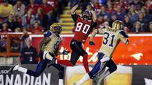 Calgary Stampeders Johnny Forzani (C) catches the ball for a touchdown between Winnipeg Blue Bombers Brandon Stewart (L) and Ian Logan during the second half of their CFL game in Calgary, Alberta, September 14, 2012. (TODD KOROL/REUTERS)