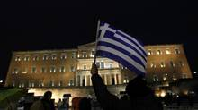 A protester holds up a Greek flag during an anti-austerity demonstration in front of the parliament in Athens February 22, 2012. (YANNIS BEHRAKIS/REUTERS)