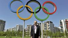 International Olympic Committee president Jacques Rogge stands under the Olympic rings during a visit to the London 2012 Olympic Village in Stratford, east London July 23, 2012. (POOL/REUTERS)
