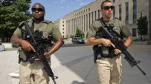 U.S. Marshals patrol the area outside federal court in Washington on July 2, 2014, where Libyan militant Ahmed Abu Khattala, charged in the deadly attack at the U.S. diplomatic outpost in Benghazi, is being held for a detention hearing. (MANUEL BALCE CENETA/ASSOCIATED PRESS)