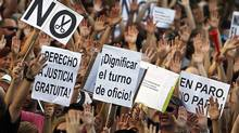 """Protesters show banners reading """" No cuts"""", """"dignify the jobs"""" and """"right to free justice"""" to demonstrate against the country's near 25 per cent unemployment rate and stinging austerity measures introduced by the government, in Madrid, Spain, Saturday, July 21, 2012. (Andres Kudacki/AP)"""