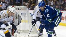 Daniel Sedin of Vancouver tries to gain control of the loose puck while being watched by former teammate and Nashville defenceman Shane O'Brien (Rich Lam/2011 Getty Images)