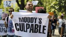 "A demonstrator in Madrid holds a banner reading ""Moody's Guilty."" (PAUL HANNA/Paul Hanna/Reuters)"