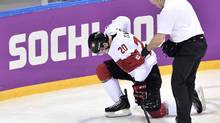 Canada forward John Tavares is helped off the ice after sustaining an injury during second period quarter-final hockey action against Latvia at the 2014 Sochi Winter Olympics in Sochi, Russia on Wednesday, February 19, 2014. (Nathan Denette/THE CANADIAN PRESS)