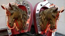 Metal horse heads outlined with neon lights adorn a horsemeat butcher shop in Paris Feb. 11, 2013. (CHARLES PLATIAU/Reuters)