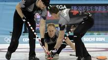 Canada's skip Brad Jacobs (C) delivers a stone between teammates lead Ryan Harnden (L) and second E. J. Harnden during their men's curling round robin session game against Great Britain at the 2014 Sochi Olympics in the Ice Cube Curling Center in Sochi February 15, 2014. (INTS KALNINS/REUTERS)