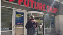 A man stands outside a closed Future Shop location at 10 Dundas St. East, in Toronto, on March 28, 2015. Sixty-five locations will re-open under the Best Buy banner.  (Jessica Lepore/GLOBE AND MAIL)