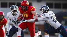 St. Francis Xavier X-Men's Mike Miller, left, and Justin Holland, right, tackle University of Calgary Dinos' Dallas Boath during first half U Sports Mitchell Bowl semifinal football action in Calgary, Saturday, Nov. 19, 2016. (Jeff McIntosh/THE CANADIAN PRESS)