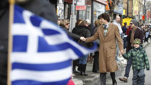 Justin Trudeau, right, with his son Xavier greet people while taking part in the Greek Independence Day parade in Montreal, March 24, 2013. (Christinne Muschi for The Globe and Mail)