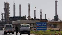 Libyan rebel fighters stand guard outside the main administration building after seizing full control of the Zawiyah oil refinery on Aug. 18, 2011. (BOB STRONG/BOB STRONG/REUTERS)
